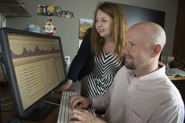 Kristine Wylie and Todd Wylie look at genomic data on their computer screen. Similar data were used to diagnose a difficult and unusual case of chronic meningitis.