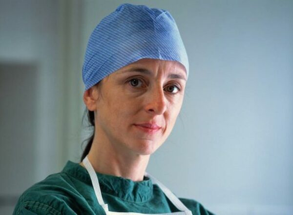 A woman wearing green scrubs and blue surgical cap looks at the camera