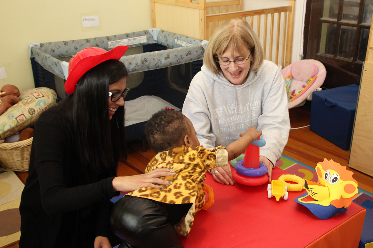 Washington University's Christine Berg (right) and occupational therapy doctoral student Jaya Bhakta involve preschooler C'dora Gilliam in active play at Our Daycare in Normandy. Occupational Therapy students work with children at the center on a range of developmental activities, among them physical behaviors aimed at preventing obesity and other problems later in life.