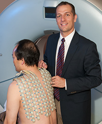 Electrophysiologist Phillip Cuculich, MD, adjusts an Electrocardiographic imaging (ECGI) vest on a patient.