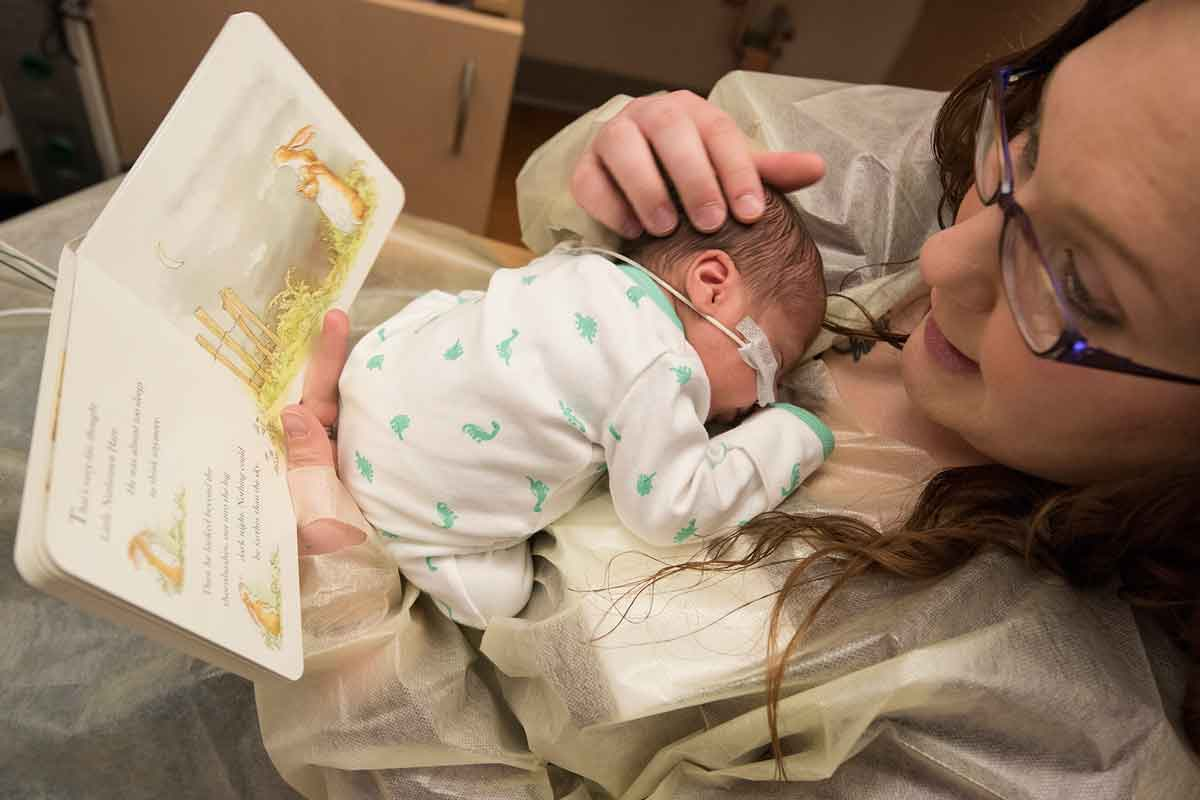 Nycole Tennant, of Trenton, Ill., reads a book to her son Kainen in the neonatal intensive care unit (NICU) at St. Louis Children's Hospital. While reading, Tennant also focuses on sensory interactions with her baby. Kainen and his twin sister, Kyzer, were born prematurely.
