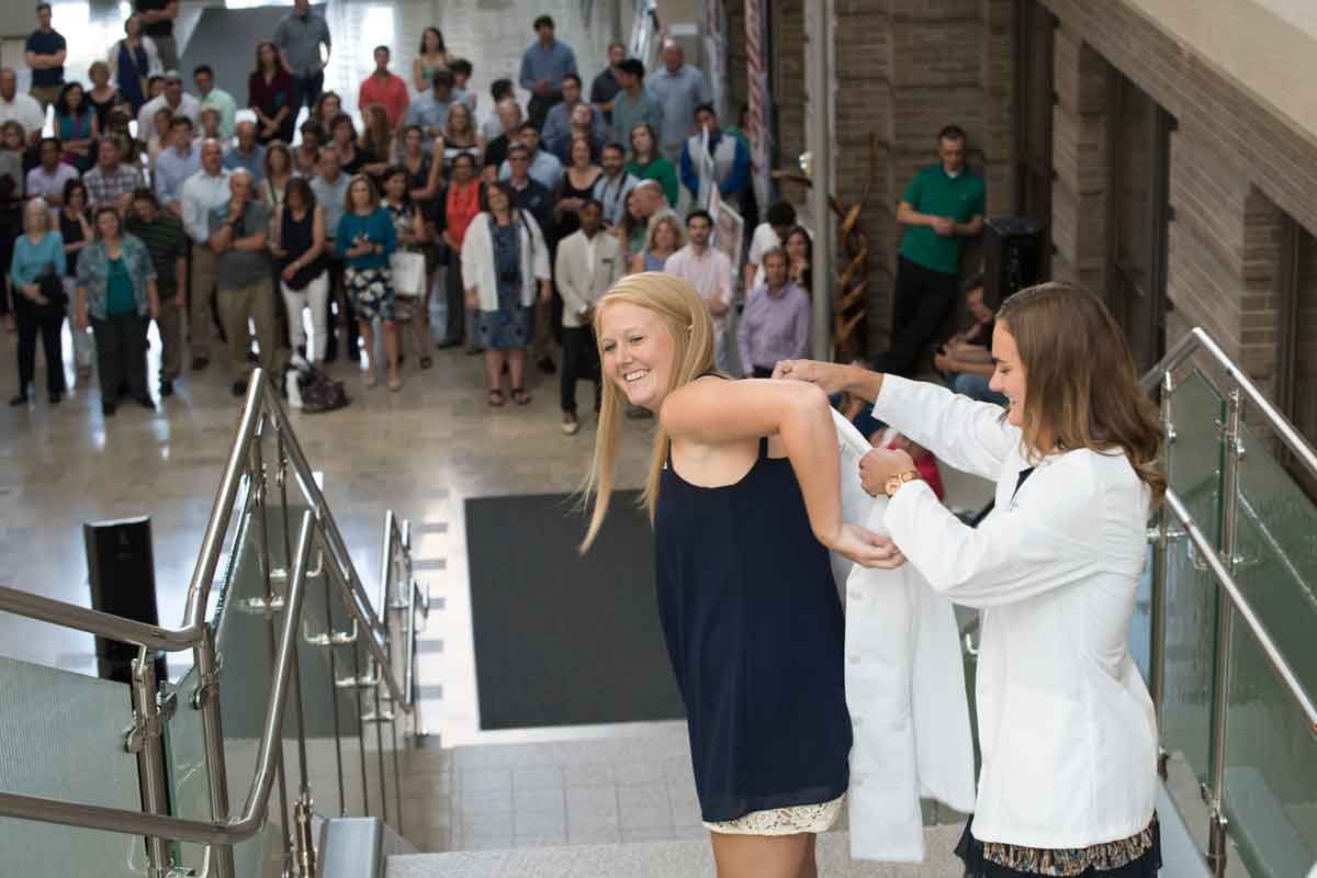 Second-year physical therapy student Torey Bird helps first-year student Krista Zerrusen into a white coat at the ceremony on the Medical Campus.