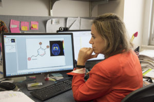 M Yanina Pepino, PhD, examines a PET image and an illustration depicting the relationship between sweets and dopamine receptors in the brain.
