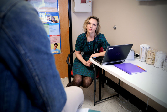 Sarah Garwood, MD, listens to a student during an exam at the clinic in Jennings Senior High School.