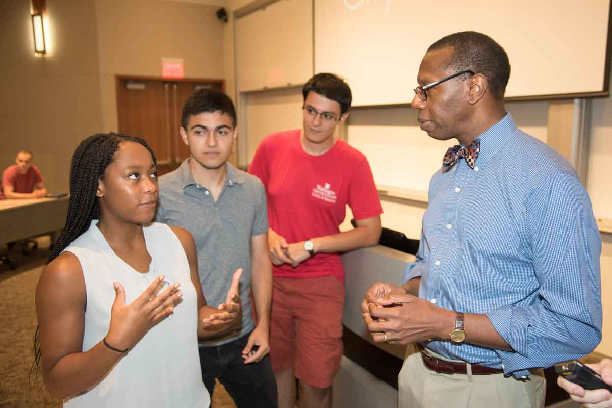 Will Ross, MD, who created and leads the Washington University Medical Plunge (WUMP) program, discusses social determinants of health with first-year medical students (from left) Marlene Kanmogne, Michael Veshkini, and Artem Arutyunov during the orientation.