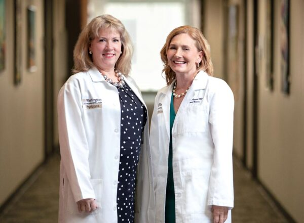 Valerie Ratts and Eva Aagaard wearing white coats and smiling into camera