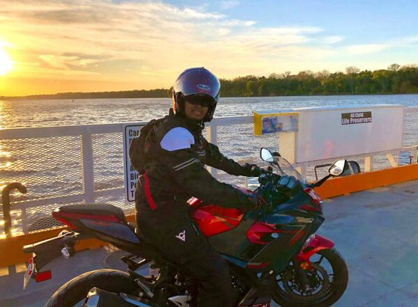 Guatam Adusumilli poses on his motorcycle wearing a jacket and helmet with a lake and sunset behind him