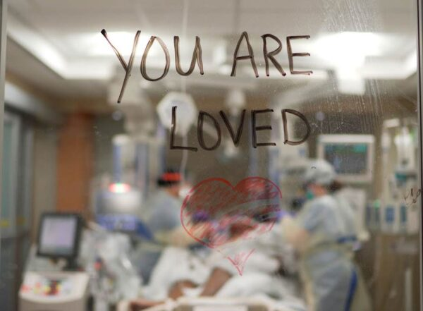 """""""You are loved"""" is written with marker on the glass window between two rooms in the hospital"""