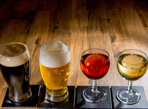 Photo showing two glasses of glasses of beer and two glasses of wine lined up on a table