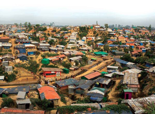 Hundreds of colorful huts cover muddy hillsides at Rohingya camp on the Bangladesh-Myanmar border.