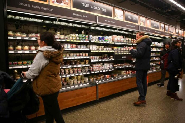 Customers browse the yogurt and deli sections in a grocery store