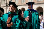 Three graduates in regalia stand and clap at outdoor ceremony