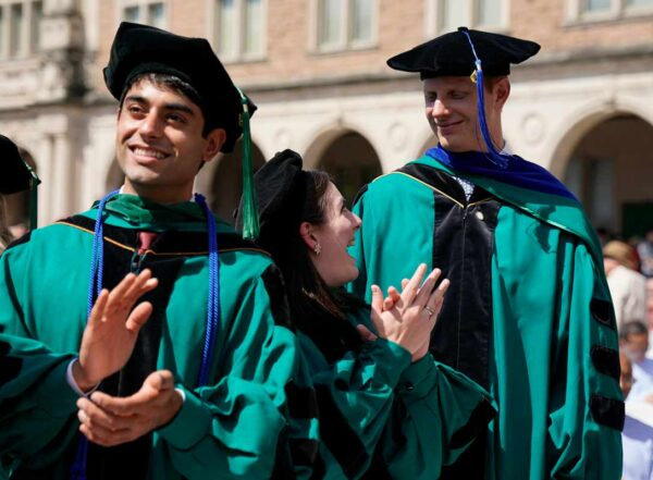 Three graduates in regalia stand and clap at outdoor ceremony