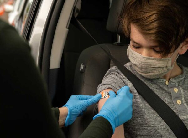 A person wearing a mask getting a bandage on their upper arm after receiving a COVID-19 vaccine