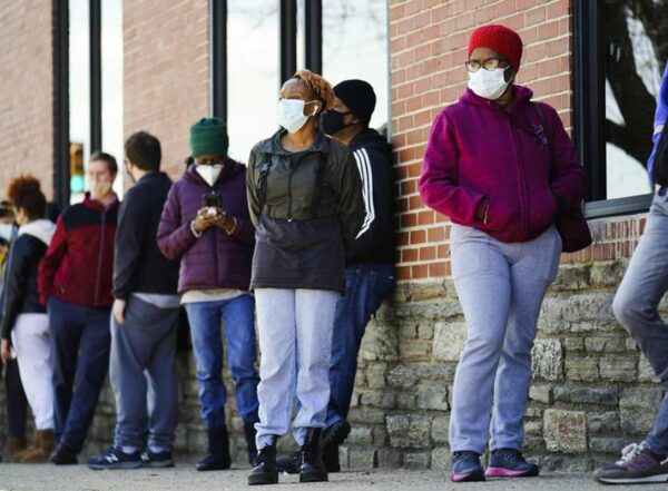 People wearing masks wait in line outside for COVID-19 vaccinations
