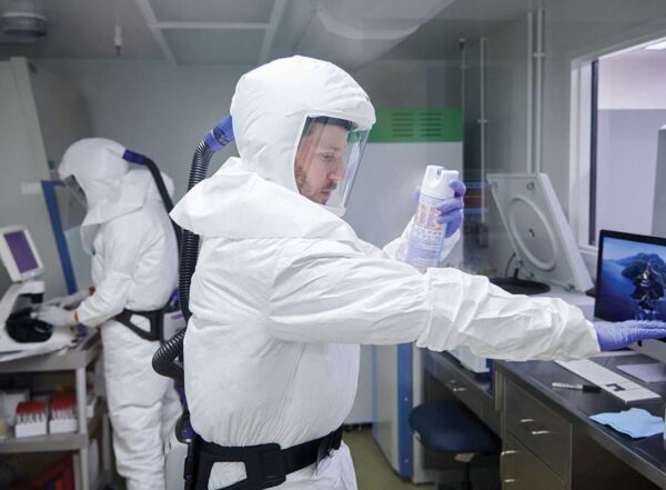 Two postdoctoral researchers wearing white biohazard suits and purple gloves work on the novel coronavirus in a biosafety level-3 lab. In the foreground, one of the researchers holds out his arm to spray his suit with an aerosol from a can.