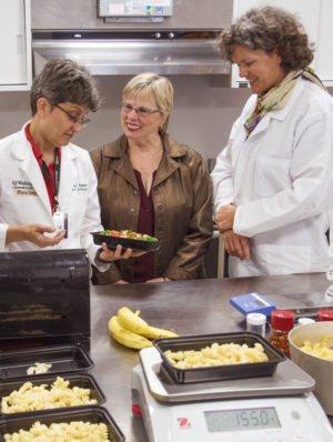 Dietitian Sue Waller (left) shows a meal to Mary Akin (center), one of the patients in a study conducted by Bettina Mittendorfer, PhD. Women in the study were provided food over the course of the research.