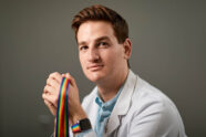 Portrait of Cory French wearing a white coat and holding a rainbow lanyard
