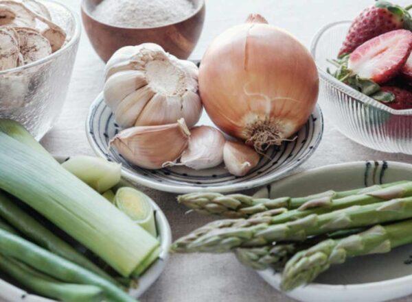 Plates of fresh vegetables including leeks, garlic and asparagus