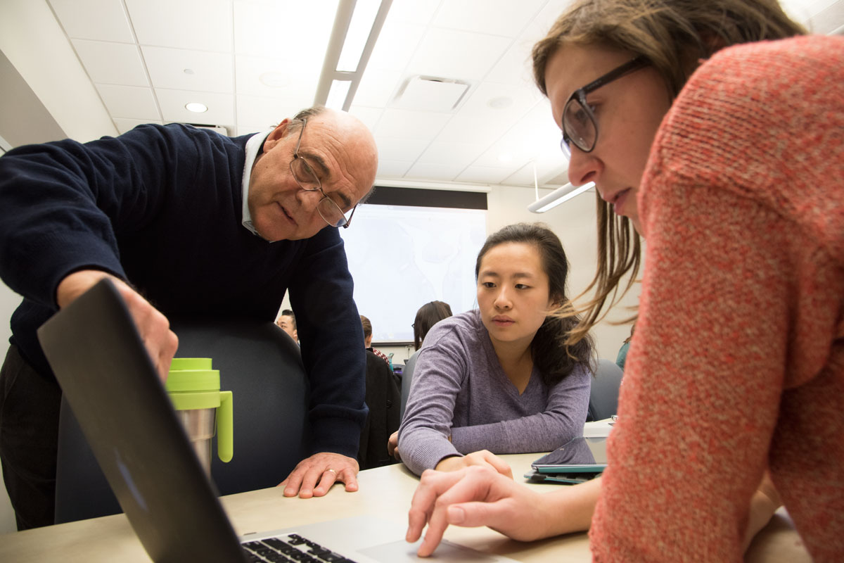 From the left, Krikor Dikranian, MD, PhD, discusses a slide in the histology iBook with medical students Jaclyn Yu and Bronwyn Bedrick.