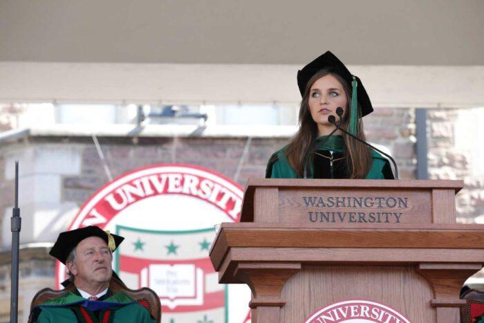 Alexandra Keane, MD, in WashU green regalia, stands at a podium to address graduates