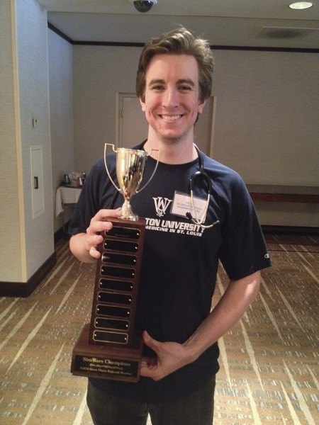 "Kevin Baumgartner holds the trophy a School of Medicine team won at the Society for Academic Emergency Medicine's Great Plains regional meeting in September 2014. The meeting included a ""SimWars"" competition, in which teams of medical students compete to solve simulated medical cases. Points are awarded based on speed, thoroughness, medical knowledge and communication skills. The team Baumgartner led won first place among several teams from medical schools in the region."