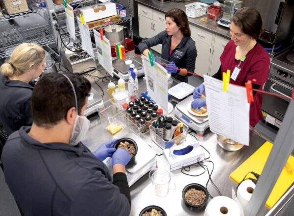 Staff members in a special metabolic kitchen gather around a stainless steel table to prepare meals for patients enrolled in a diet and metabolism study