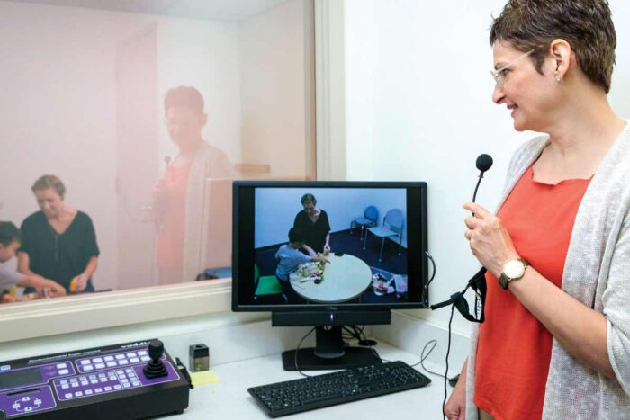 Joan Luby, MD, observes a parent and child through a one-way mirror and, using a microphone and earpiece.