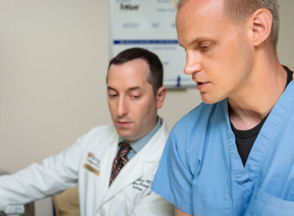 Medical student Weston McCarron (right), practices performing an ultrasound with Evan Schwarz, MD