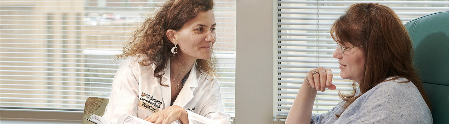 Laura Piccio, MD, talks with a patient during a checkup.