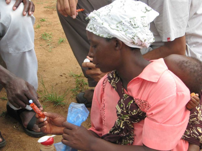 Parents of severely malnourished children in Malawi learn how to measure doses of medication.
