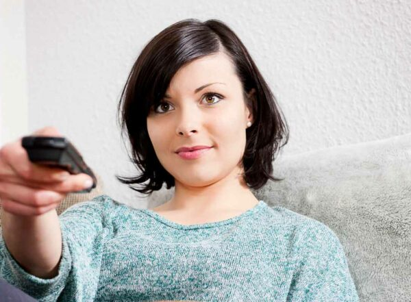Young woman sits on couch pointing remote