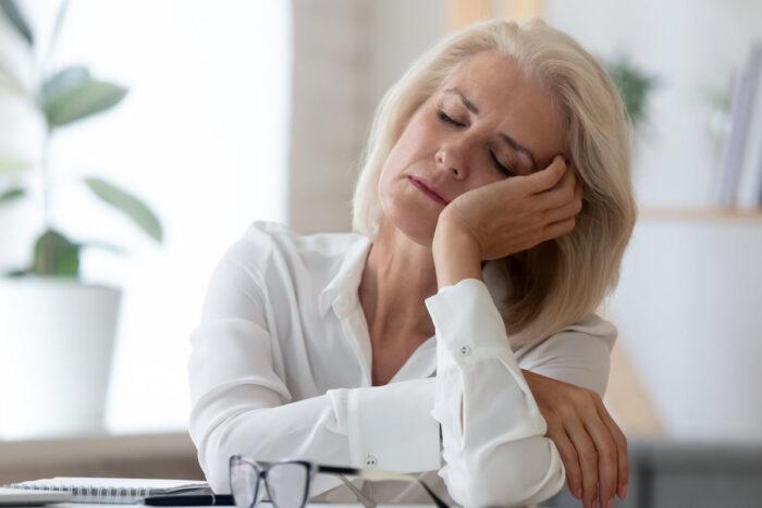 A woman sitting at a desk nods to sleep