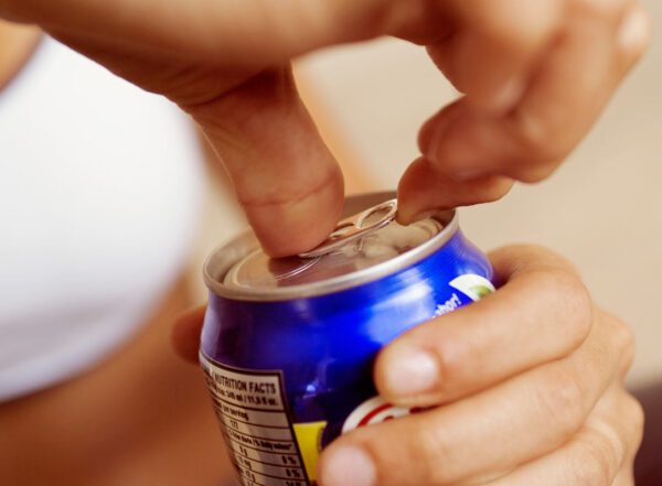 A person opens a can of a soft drink