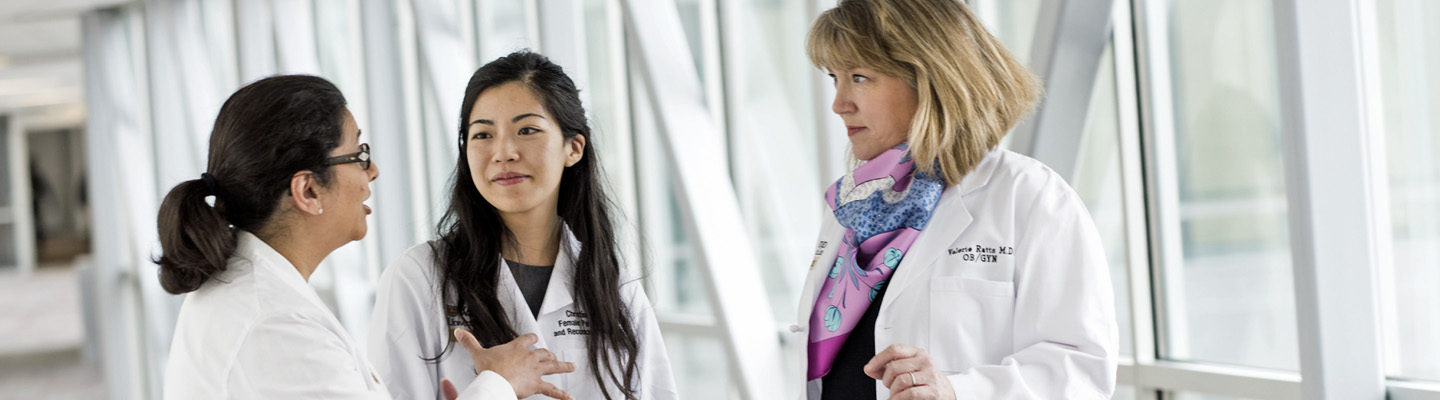 Department of Ob/Gyn faculty members Premal H. Thaker, MD, MS, Christine Chu, MD, and Valerie Ratts, MD, talk in a bright hallway on the Medical Campus.
