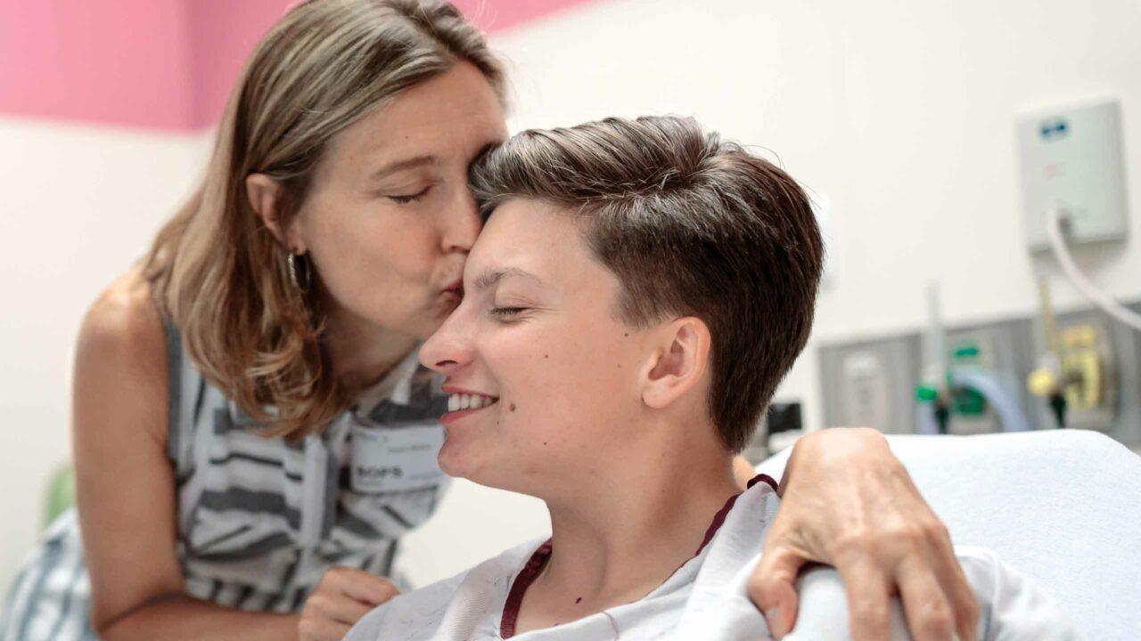 Karen Stokes kisses her transgender son, Chase, as he prepares for surgery.